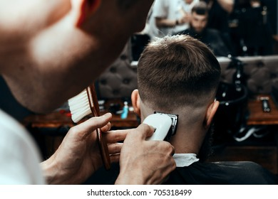 BARBERSHOP THEME. BARBER IS TRIMMING THE HAIRCUT OF HIS YOUNG SERIOUS CLIENT. HE IS USING A HAIR CLIPPER