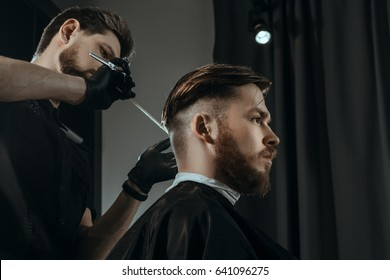 BARBERSHOP THEME. BEARDED BARBER IN BLACK RUBBER GLOVES IS TRIMMING THE HAIRCUT OF HIS YOUNG SERIOUS CLIENT. HE IS USING A HAIR CLIPPER