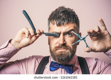 Barbershop tools. Professional hairstylist in barbershop. Bearded stylish man with scissors and straight razor