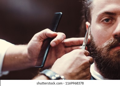 Barbershop with wooden interior. Bearded model man and barber