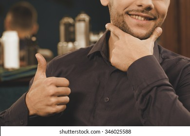 Barbershops rule. Cropped closeup of a man touching his beard smiling widely and showing thumbs up