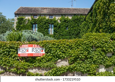 BARBIZON, FRANCE - MAY 16, 2020. Prestigious property, covered with ivy on a background of blue sky. A real estate agency sign indicates in French: FOR SALE.