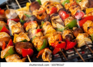 Bar-B-Q or BBQ with kebab cooking. coal grill of chicken meat skewers with mushroom and peppers. barbecuing dinner