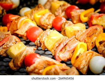 Bar-B-Q or BBQ with kebab cooking. Coal grill of pork skewers with tomatoes, onion and peppers. barbecue camping dinner.