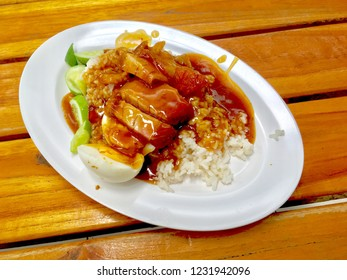 barbuced crispy pork in red sauce with rice - One of the most popular menu in this era of Thailand. Let's look at the hot rice, crispy pork with crispy salty red sauce.