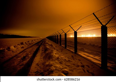 Barbwire fence on snowy field. Strong spotlights in back. Night shot.