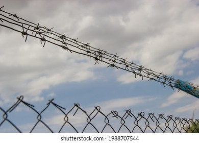 Barbwire on a fence in front of a cloudy sky
