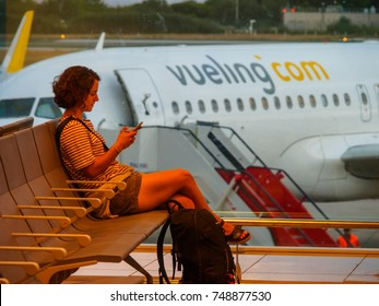 BARCELONA AIRPORT, BARCELONA, SPAIN - August 21, 2017: Killing time with smart phone in the airport waiting for a Vueling flight