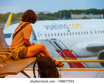 BARCELONA AIRPORT, BARCELONA, SPAIN - August 21, 2017: Back view of a woman  seated looking at a Vueling plane