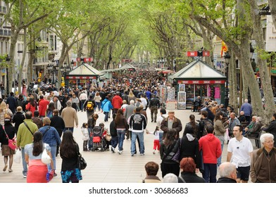 BARCELONA - APRIL 16: People walk by at the famous La Rambla  April 16, 2009 in Barcelona, Spain.