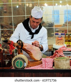 BARCELONA - APRIL 30: April fair in Barcelona - 2010 lasts 5 days. Cook from Andalusia cuts a smoked gammon. April, 30, 2010, Barcelona, Spain, Catalonia