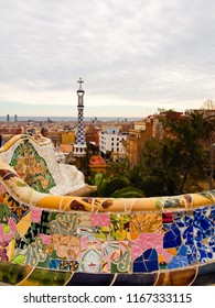 Barcelona, barcelona/spain - 1/29/2014: Beautiful view of ceramic mosaic tiles decorated wall of nature square of park guell overlooking the neighborhood of downtown of Barcelona Spain