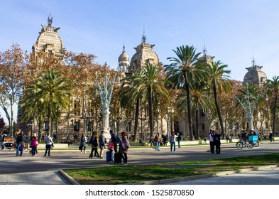 Barcelona, Catalonia, Spain - 01.29.2019:  Tourists walk around the palm tree lined square adjacent to the Superior Court of Justice of Catalonia, on the Passeig de Lluis Companys.