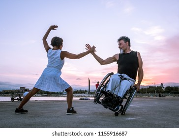 Barcelona, Catalonia / Spain - August 2018: A man in a wheelchair dances with a woman on the beach