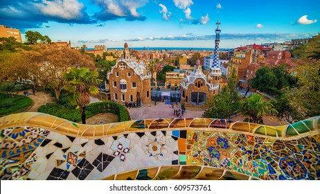 Barcelona, Catalonia, Spain: the Park Guell of Antoni Gaudi at sunset. The two buildings at the entrance of the park and Gaudi's mosaic work on the main terrace.