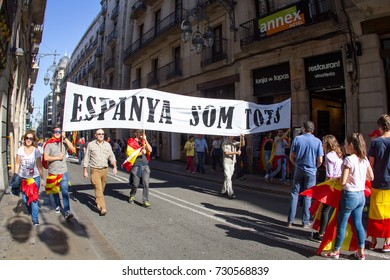 """BARCELONA, CATALONIA, SPAIN - October 08, 2017: Protesters rally (demonstration) against Catalan independence in Barcelona, people with  flags and billboard with slogan """"Espanya som tots""""."""