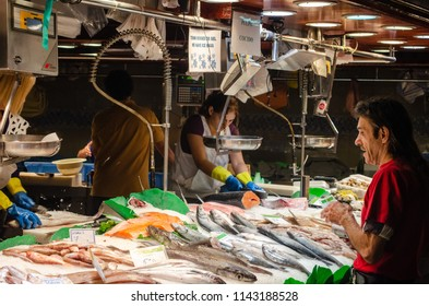 Barcelona, Catalonia, Spain - October 15, 2013: A customer is buying seafood from fishmongers stall at La Boqueria Market.