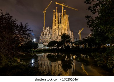 Barcelona, Catalonia, Spain - October 6, 2019: A night view of the east Nativity facade of The Basílica de la Sagrada Família reflected in a small pond and illuminated by bright surrounding lights.