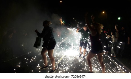 Barcelona, Catalonia, Spain - September, 23, 2017. Correfoc, typical catalan celebration in which devils armed with fireworks dance through the streets. Tourist dancing under sparks. La Merce.