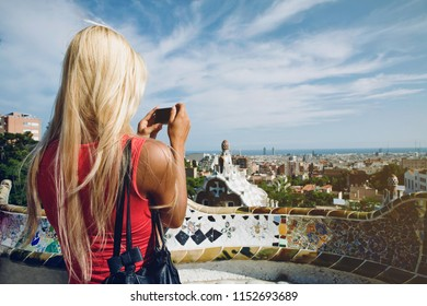 """""""Barcelona, Catalonia/Spain- 09/13/2010: Blondy caucasian Girl taking picture of Barcelona from the terrace of of Park Guell, architectural landmark designed by the famous architect Antonio Gaudi"""""""