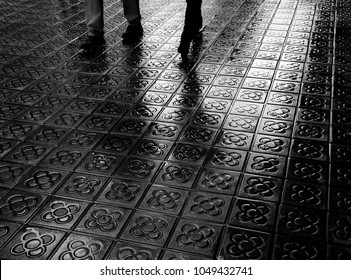 Barcelona. Couple legs and their reflection on wet flower street paving. Romantic vacation background. Black and white photo.