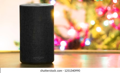 BARCELONA - DECEMBER 06: Alexa personal smart loudspeaker device on a wooden shelf against a christmas tree lighting in a home livingroom on December 6, 2018 in Barcelona