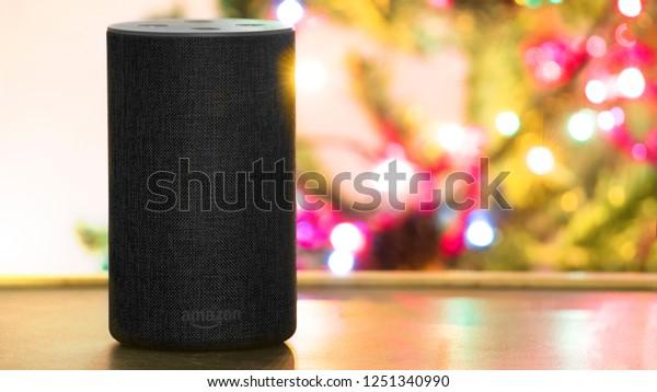 BARCELONA - DECEMBER 06: Alexa personal smart loudspeaker device on a wooden shelf against a christmas tree lighting in a home livingroom on December 6, 2018 in Barcelona