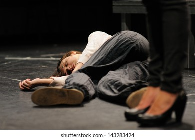 BARCELONA - JAN 13: An actress, in the floor after being poisoned, of the Barcelona Theater Institute, plays in the comedy Shakespeare For Executives on January 13, 2013 in Barcelona, Spain.