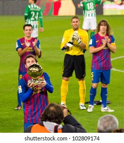 BARCELONA - JANUARY 15: Lionel Messi shows his third FIFA World Player Gold Ball Award to the soccer supporters of Football Club Barcelona, on January 15, 2012 in Nou Camp stadium, Barcelona, Spain.