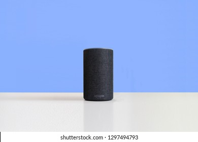 BARCELONA, JANUARY 28: Amazon Alexa device on a white wooden shelf against an empty plain blue background on January 28, 2019 in Barcelona.