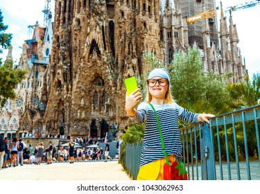 Barcelona - July, 10, 2017: modern child in yellow shorts and stripy shirt in Barcelona, Spain with cellphone taking selfie