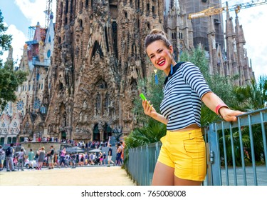 Barcelona - July, 10, 2017: smiling modern traveller woman in yellow shorts and stripy shirt near Sagrada Familia in Barcelona, Spain writing sms