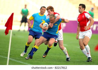 BARCELONA - JULY 9: Pavlo Masiukov of Ukraine is tackled by Welsh player during the match of Rugby7 European Championship between Ukraine and Wales at the Olympic Stadium in Barcelona, on July 9, 2011