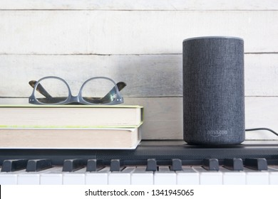 BARCELONA, MARCH 15: Alexa Echo smart speaker for IoT and home automation on a piano next to some books against a wooden background on March 15, 2019 in Barcelona