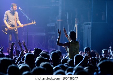 BARCELONA - MAY 16: A girl (fan) from the audience clapping and screaming in front of his favourite guitarist in a concert at Razzmatazz discotheque on May 16, 2014 in Barcelona, Spain.