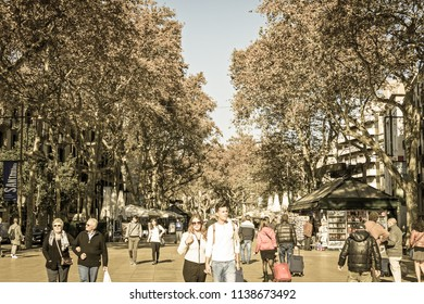 BARCELONA- NOV 15: The famous Ramblas street with walking tourists on November 15, 2016. the Ramblas is the most popular street in Barcelona, Spain. Image with vintage and yesteryear effect