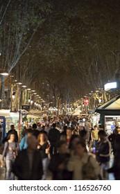 BARCELONA - NOVEMBER 8:: Tourists visits La Rambla street at night in Barcelona. La Rambla  is popular with both tourists and locals alike. November 8, 2011 in Barcelona (Spain).