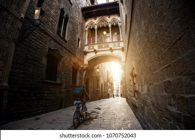 Barcelona people biking bicycle in Barri Gothic Quarter and Bridge of Sighs in Barcelona, Catalonia, Spain.