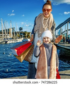 in Barcelona for a perfect present. Full length portrait of happy elegant mother and daughter with shopping bags on embankment in Barcelona, Spain handwaving