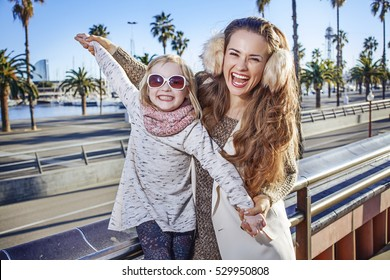 in Barcelona for a perfect winter. Portrait of happy trendy mother and child travellers on embankment in Barcelona, Spain having fun time