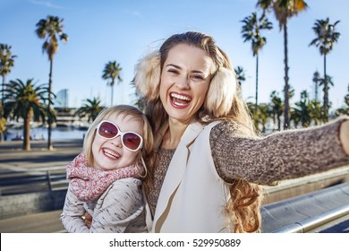 in Barcelona for a perfect winter. smiling young mother and daughter tourists on embankment in Barcelona, Spain taking selfie