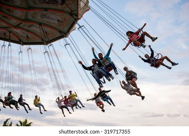 BARCELONA - SEP 5: People have fun at the carousel flying swing ride attraction at Tibidabo Amusement Park on September 5, 2015 in Barcelona, Spain.