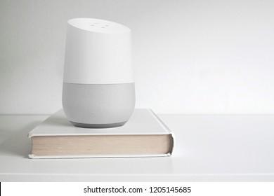 BARCELONA - SEPTEMBER 2018: Google Home smart speaker on a book on a shelf on October 17, 2018 in Barcelona.