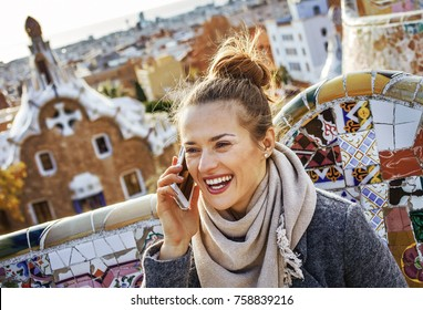 Barcelona signature style. happy young traveller woman in coat at Guell Park in Barcelona, Spain speaking on a cell phone