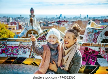 Barcelona signature style. Portrait of happy trendy mother and child travellers in Barcelona, Spain pointing on something while sitting on a bench