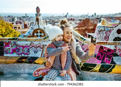 Barcelona signature style. Portrait of happy trendy mother and child tourists at Guell Park in Barcelona, Spain with digital camera taking photo while sitting on a bench