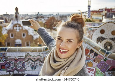 Barcelona signature style. smiling elegant tourist woman in coat at Guell Park in Barcelona, Spain with mobile phone taking photo
