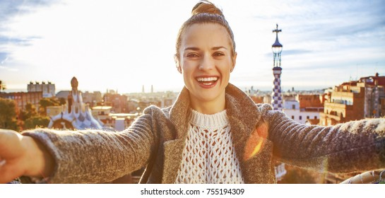 Barcelona signature style. smiling modern tourist woman in coat at Guell Park in Barcelona, Spain taking selfie