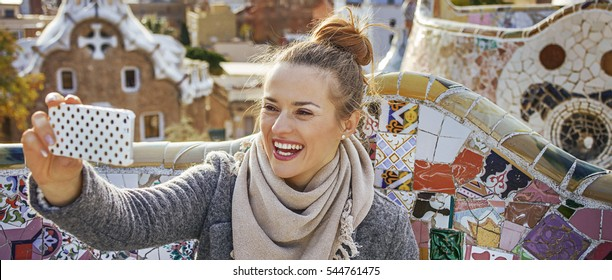 Barcelona signature style. smiling trendy traveller woman in coat at Guell Park in Barcelona, Spain with mobile phone taking selfie