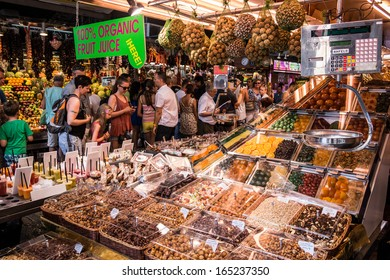 BARCELONA, SPAIN - 02 JULY 2013: People visit and buy food in the most famous market in the city called La Boqueria in Barcelona. Barcelona July 2, 2013.